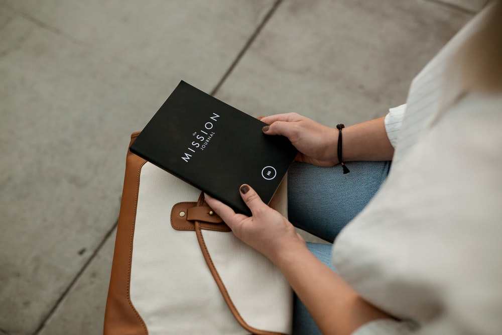 woman holding black Mission book