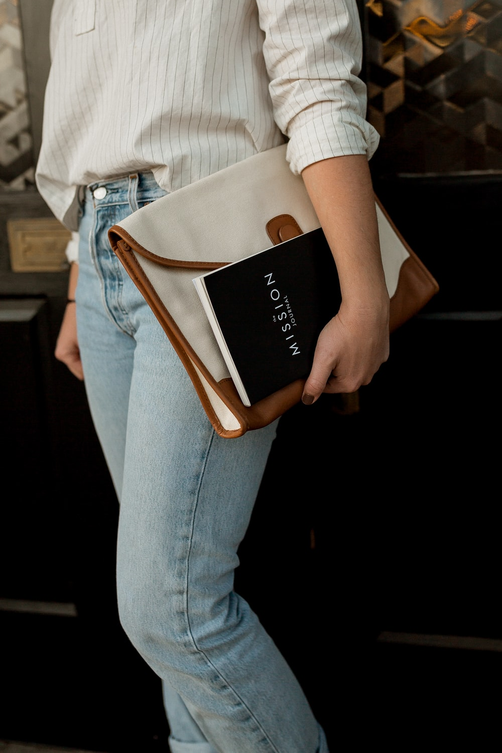 woman carrying white and brown leather bag