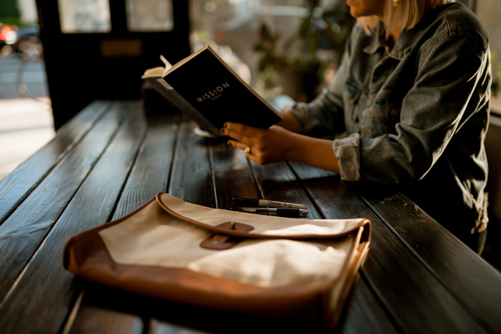 person reading a book on table