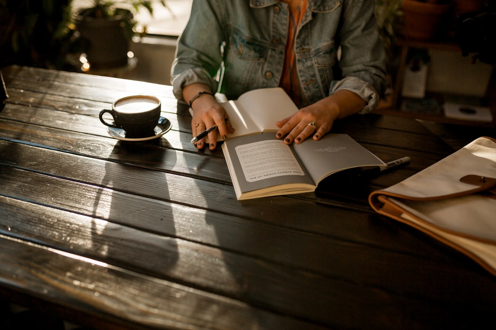 person opening notebook on brown wooden table
