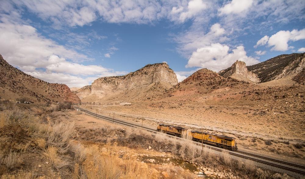 steel locomotive in railway traveling in between mountains
