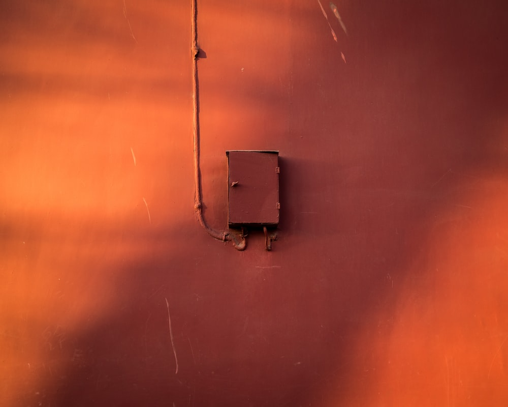 photo of brown power distribution box mountain on wall