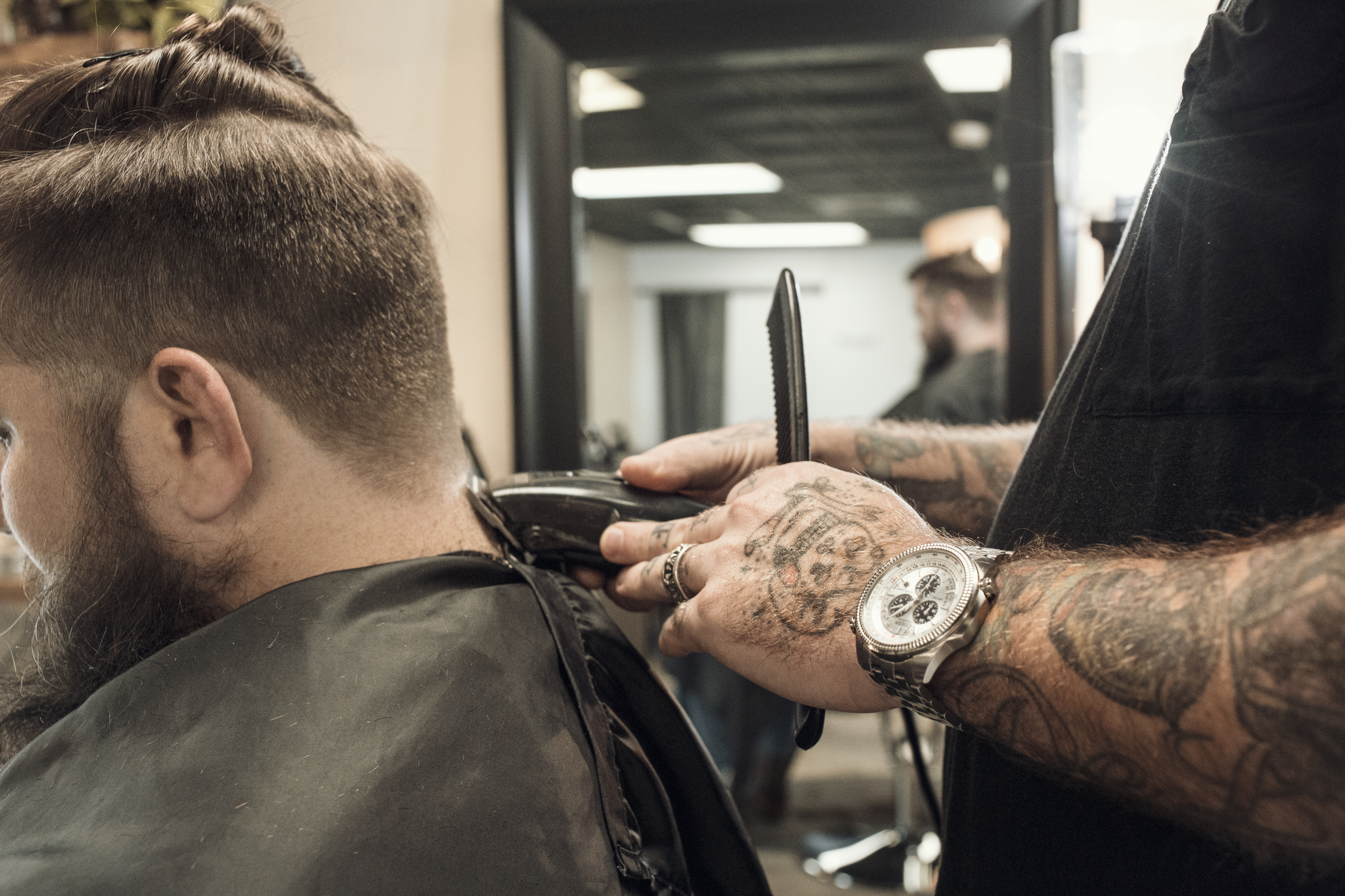 """Dustin, our talented and inked up barber at Whiskey Neat Barbershop, working on a fade and beard trim."""