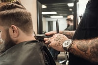 """""""Dustin, our talented and inked up barber at Whiskey Neat Barbershop, working on a fade and beard trim."""""""