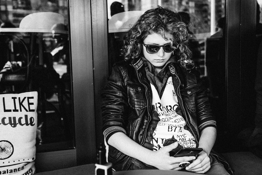 greyscale photo of sitting woman using smartphone