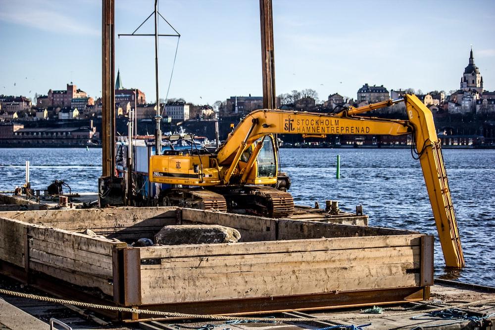 yellow excavator on top of metal platform above sea