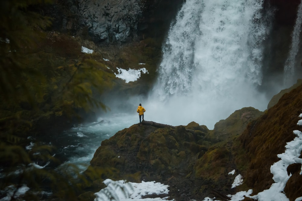 man standing beside waterfalls