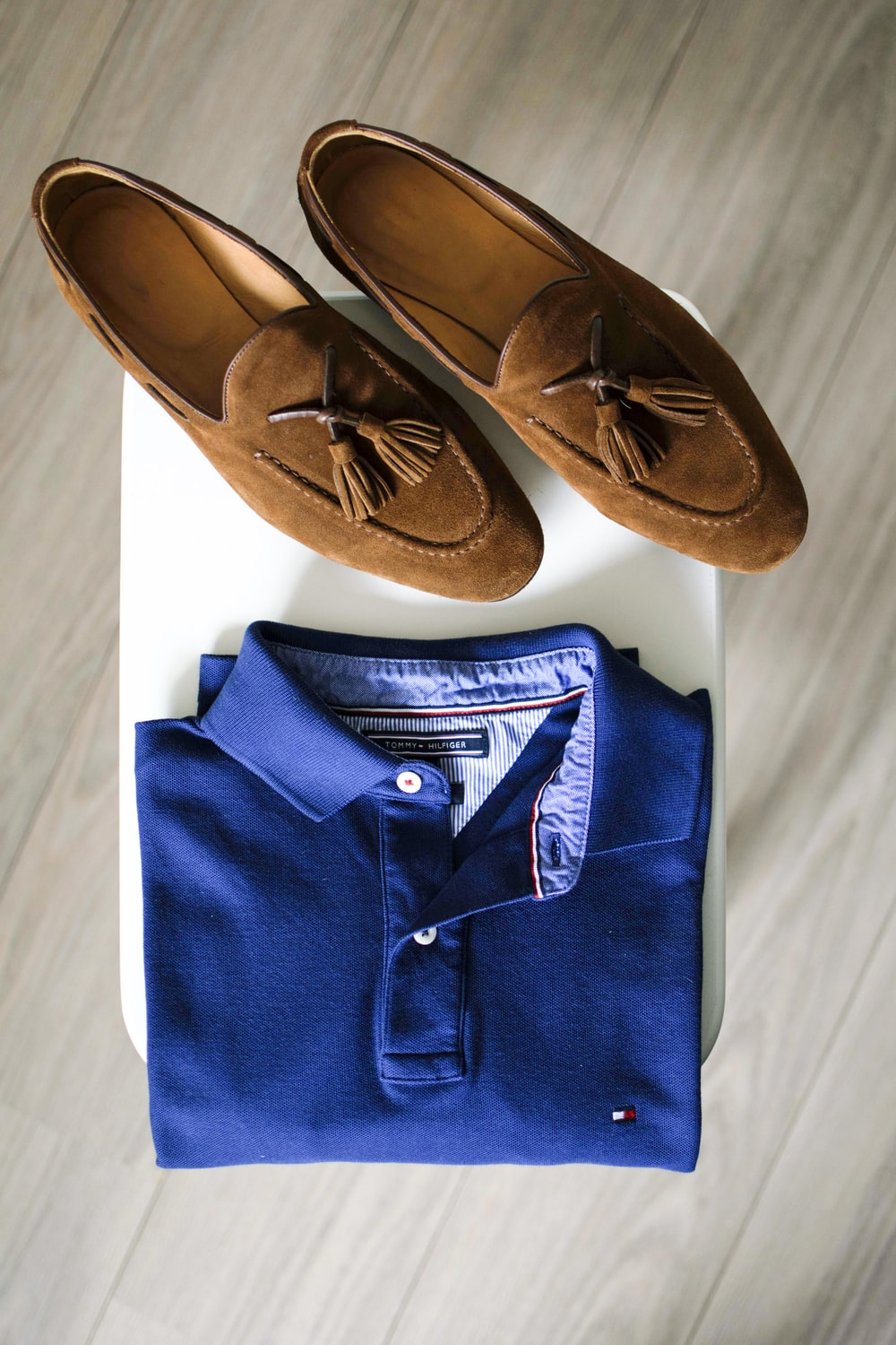 pair of brown loafers and blue polo shirt