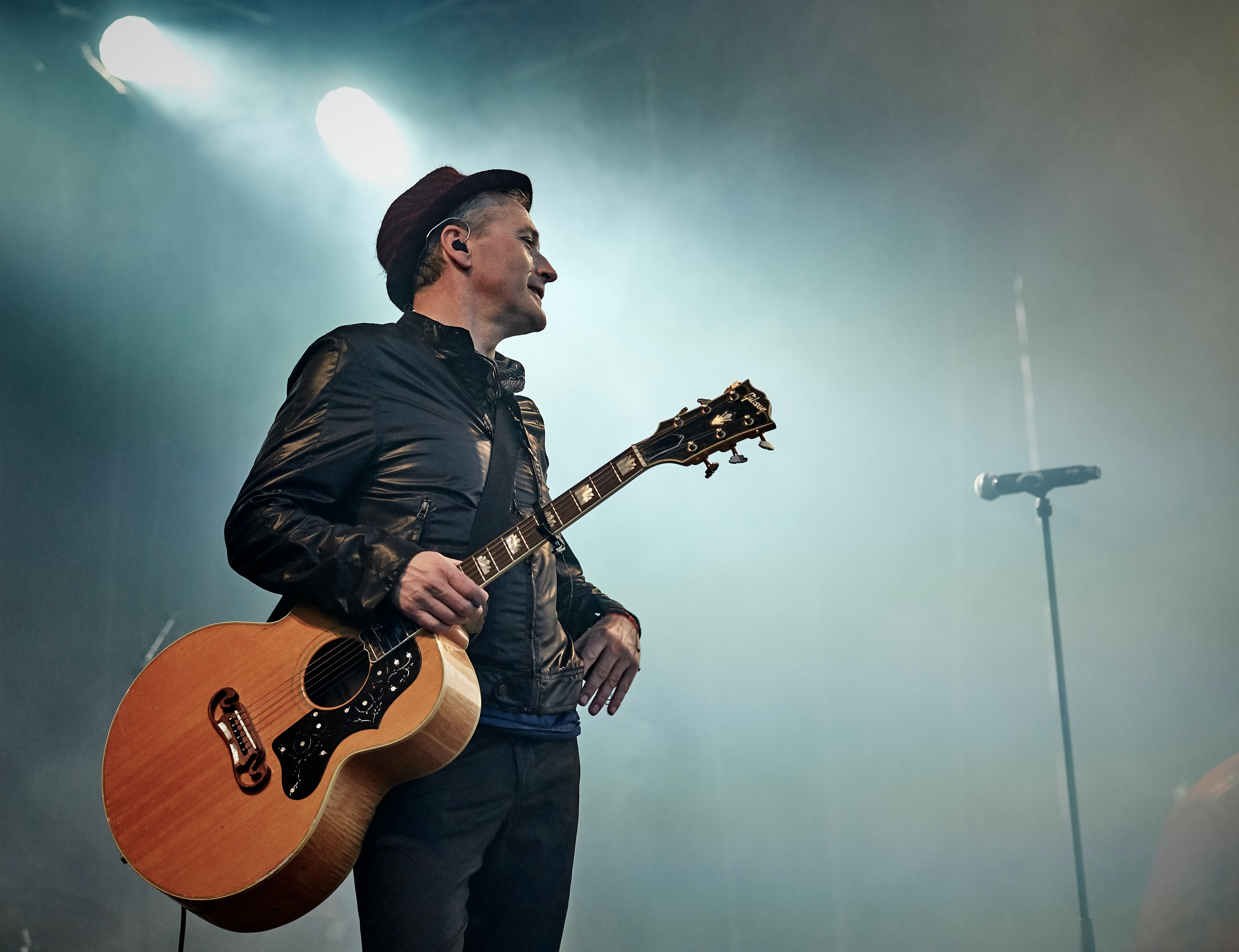 man holding acoustic guitar beside microphone with stand