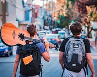 two man carrying backpacks during daytime