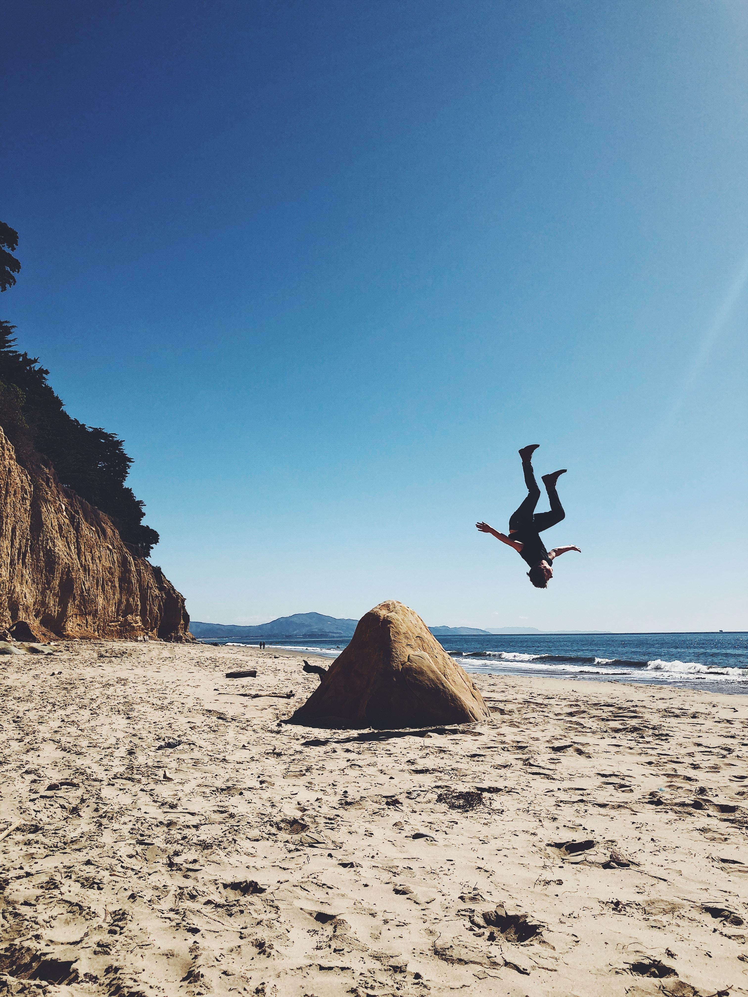 man back lifting on shore at daytime