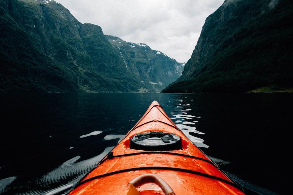 orange canoe on lake surrounding with mountain at daytime