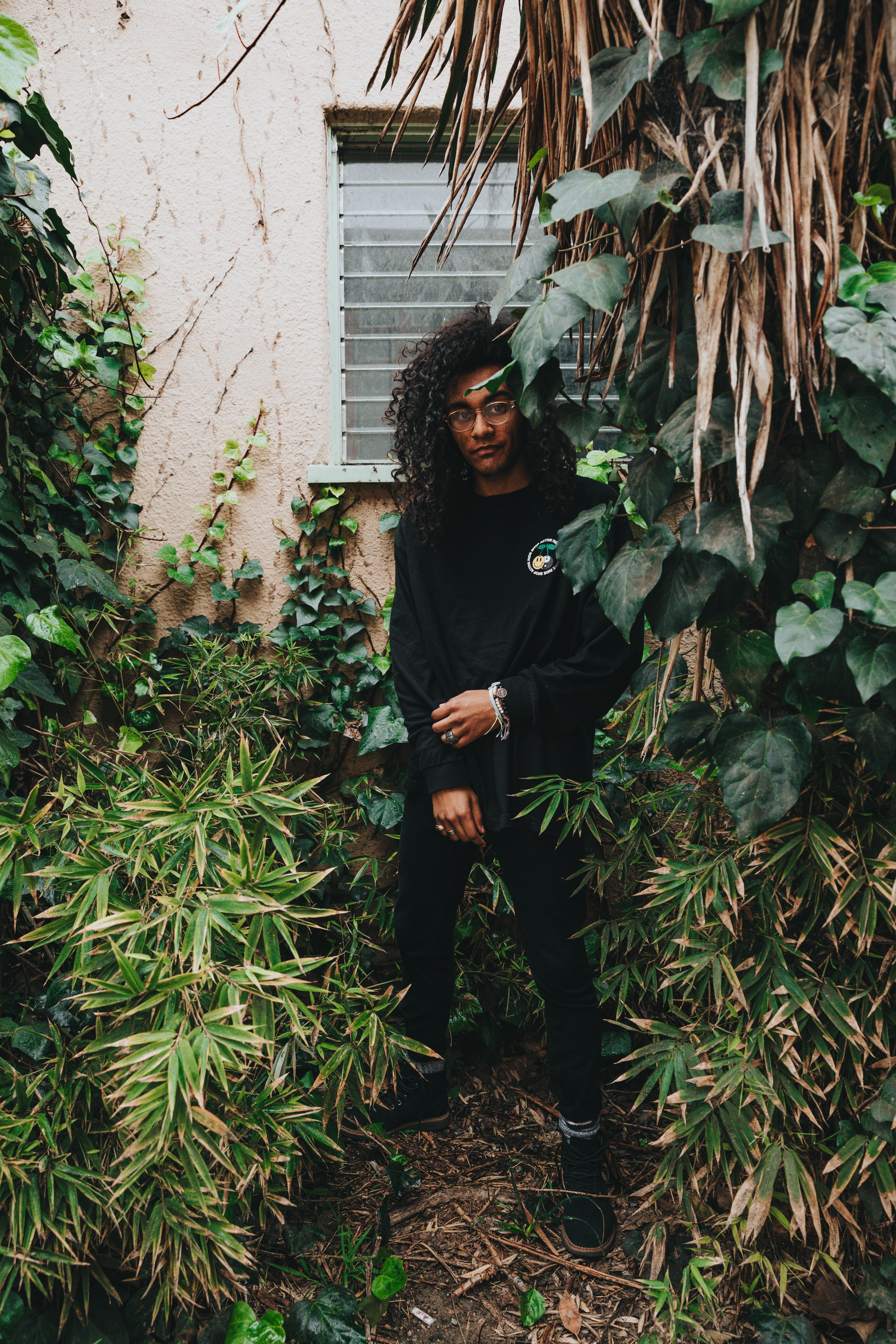 man in black sweatshirt standing near window