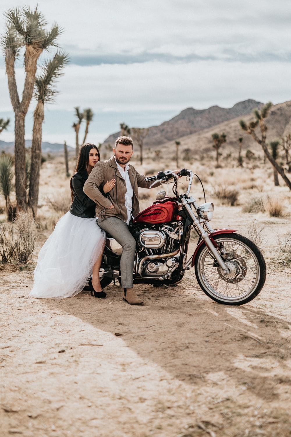 man and woman sitting on motorcycle