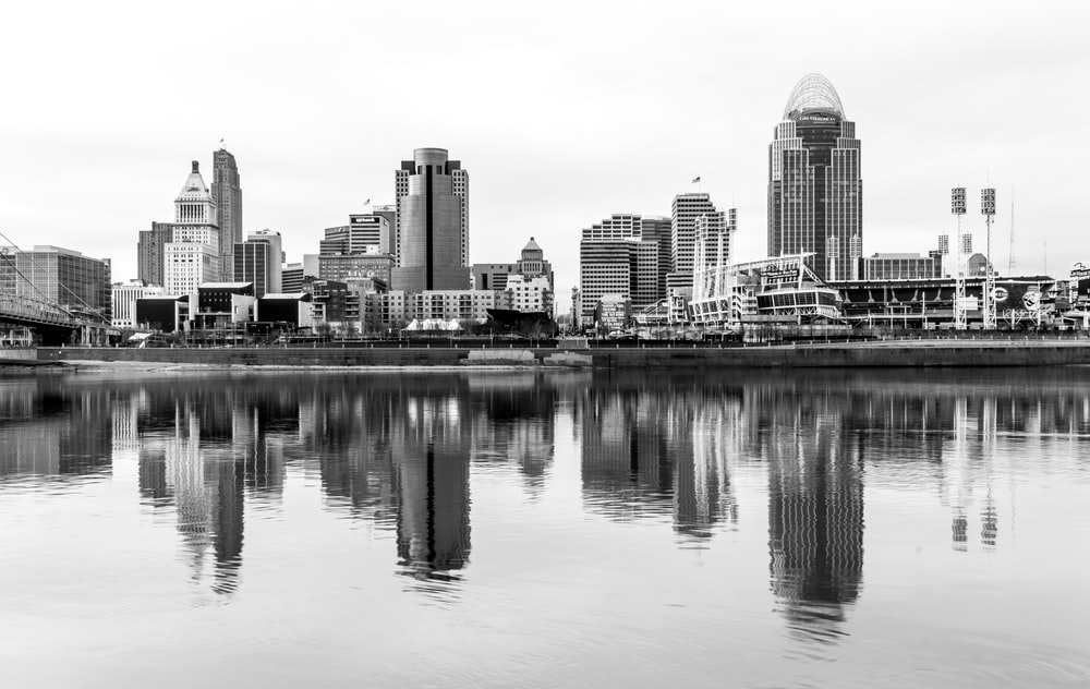 body of water near high rise building in grayscale photography
