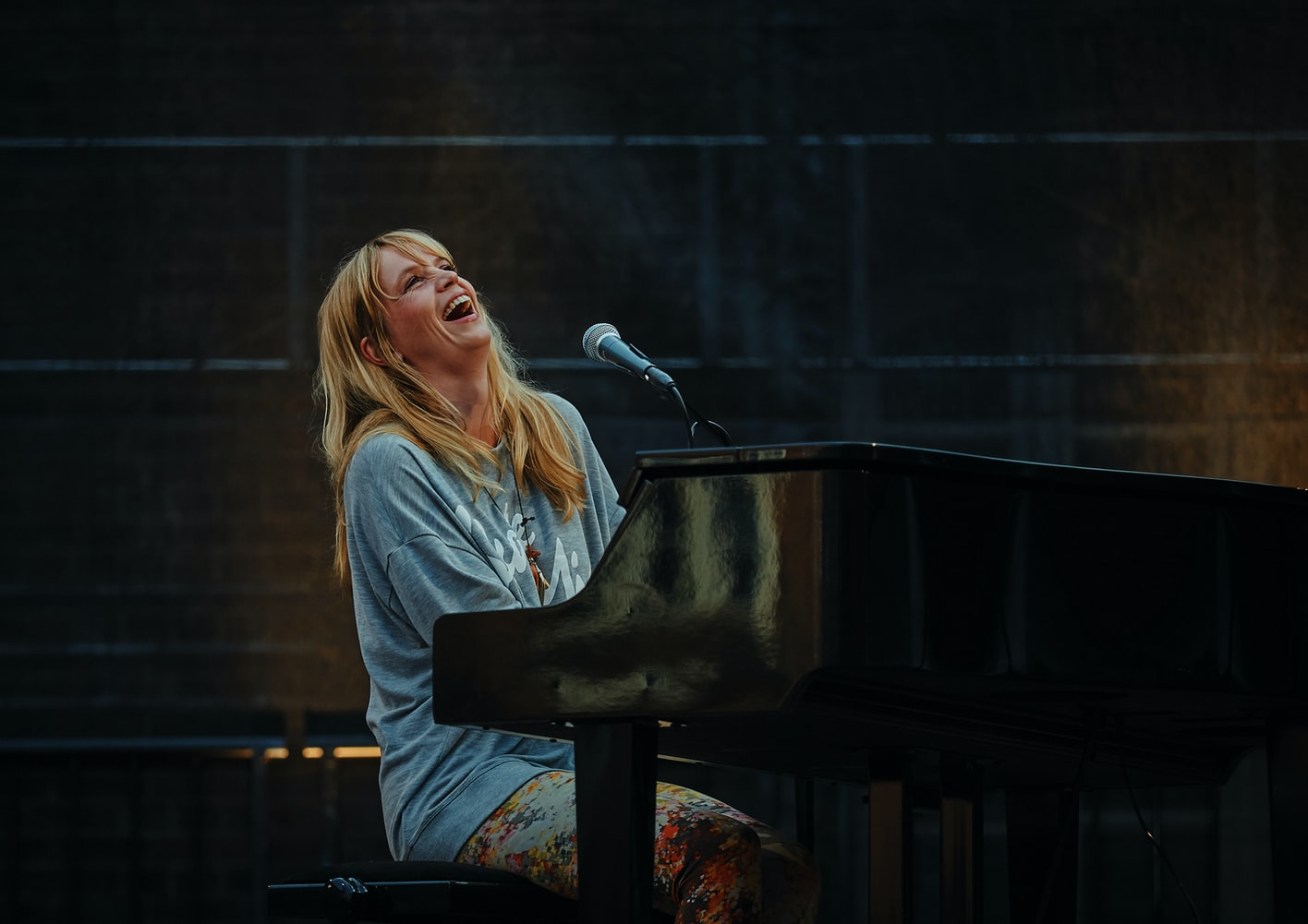 Woman performing at a grand piano on stage laughing and looking up.