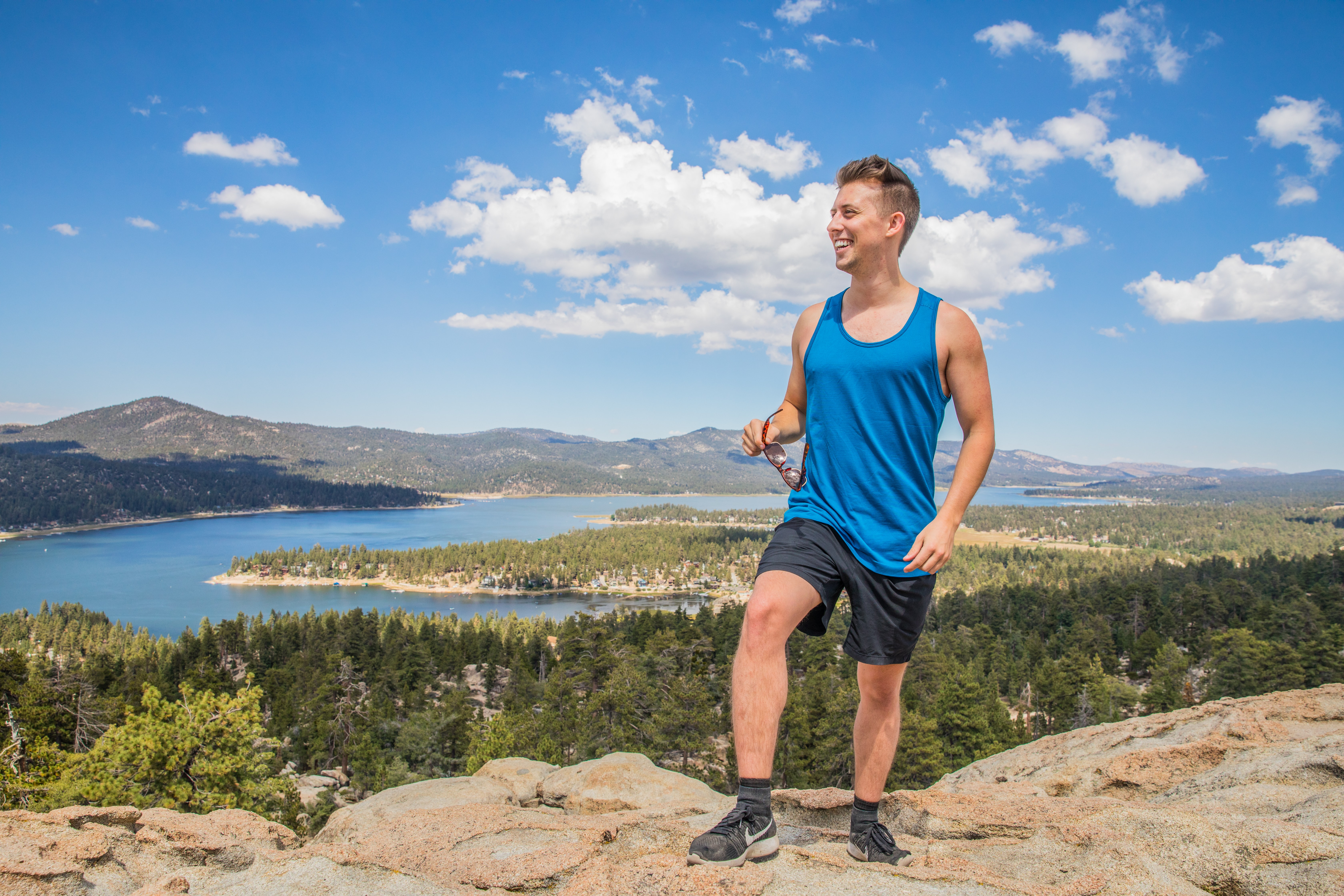 man wearing blue tank top and black shorts standing on rock cliff