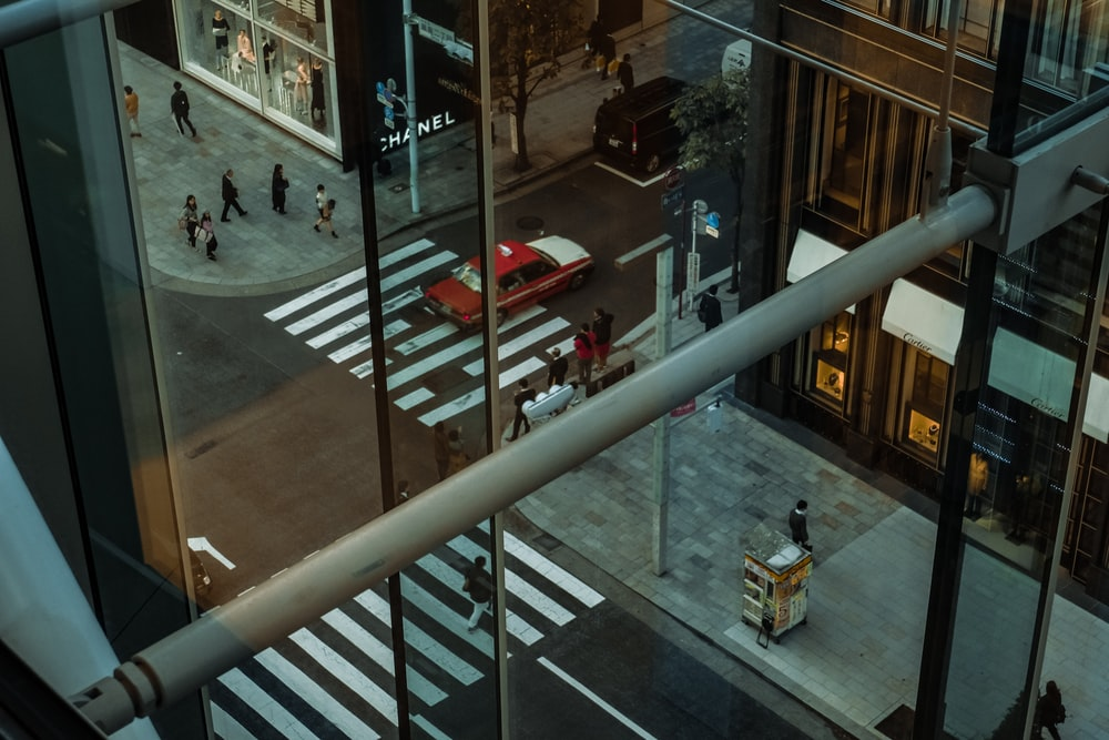 photography of people walking on street reflected on building window