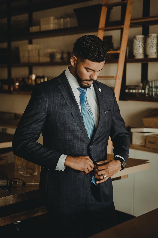 man wearing black coat standing near brown kitchen counter
