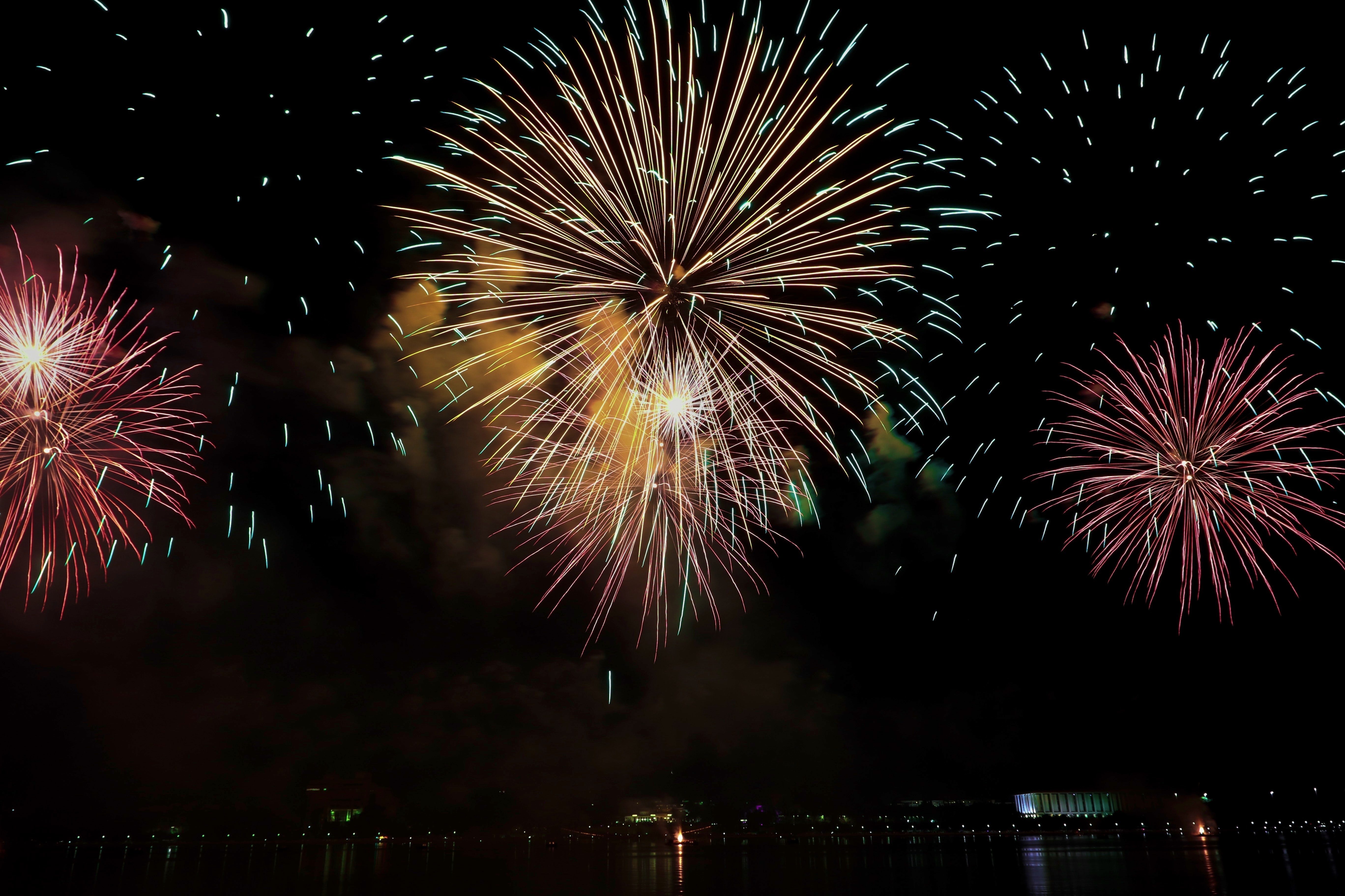 yellow and pink fireworks display in sky
