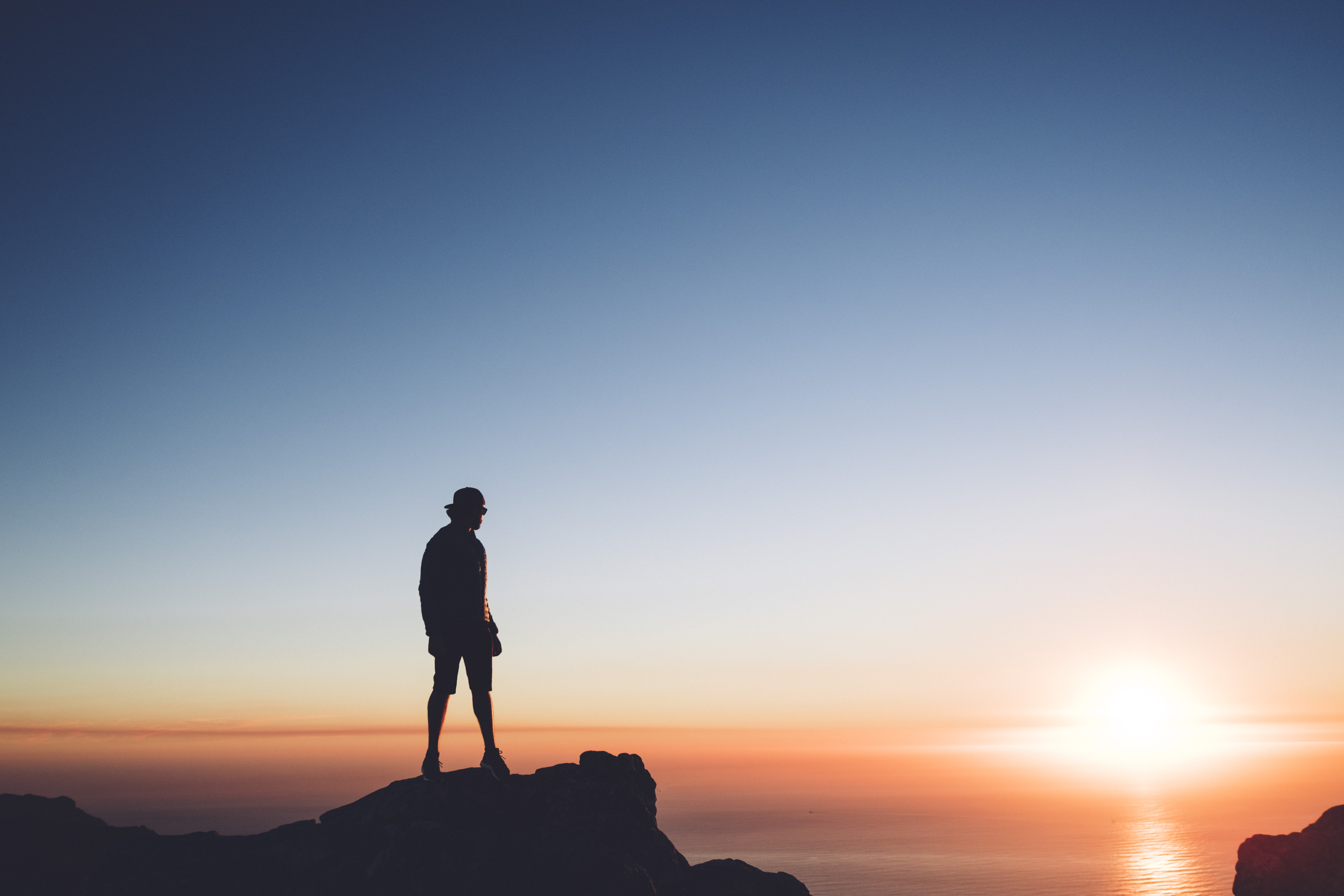 silhouette photo of man standing on peak front of the sea