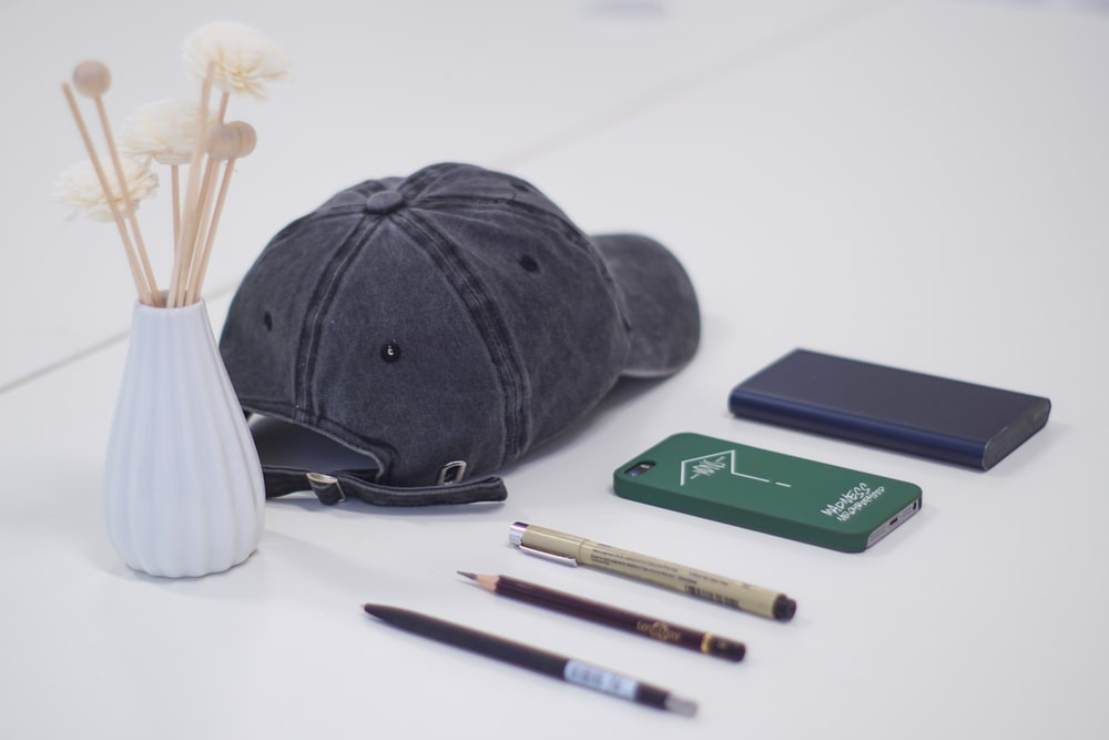 gray fitted cap, three pen, smartphone, and blue power bank on white surface