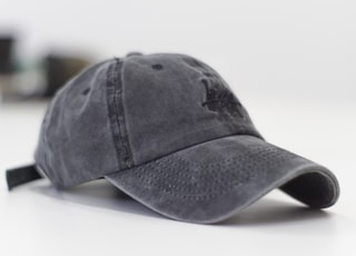 gray baseball cap on white surface