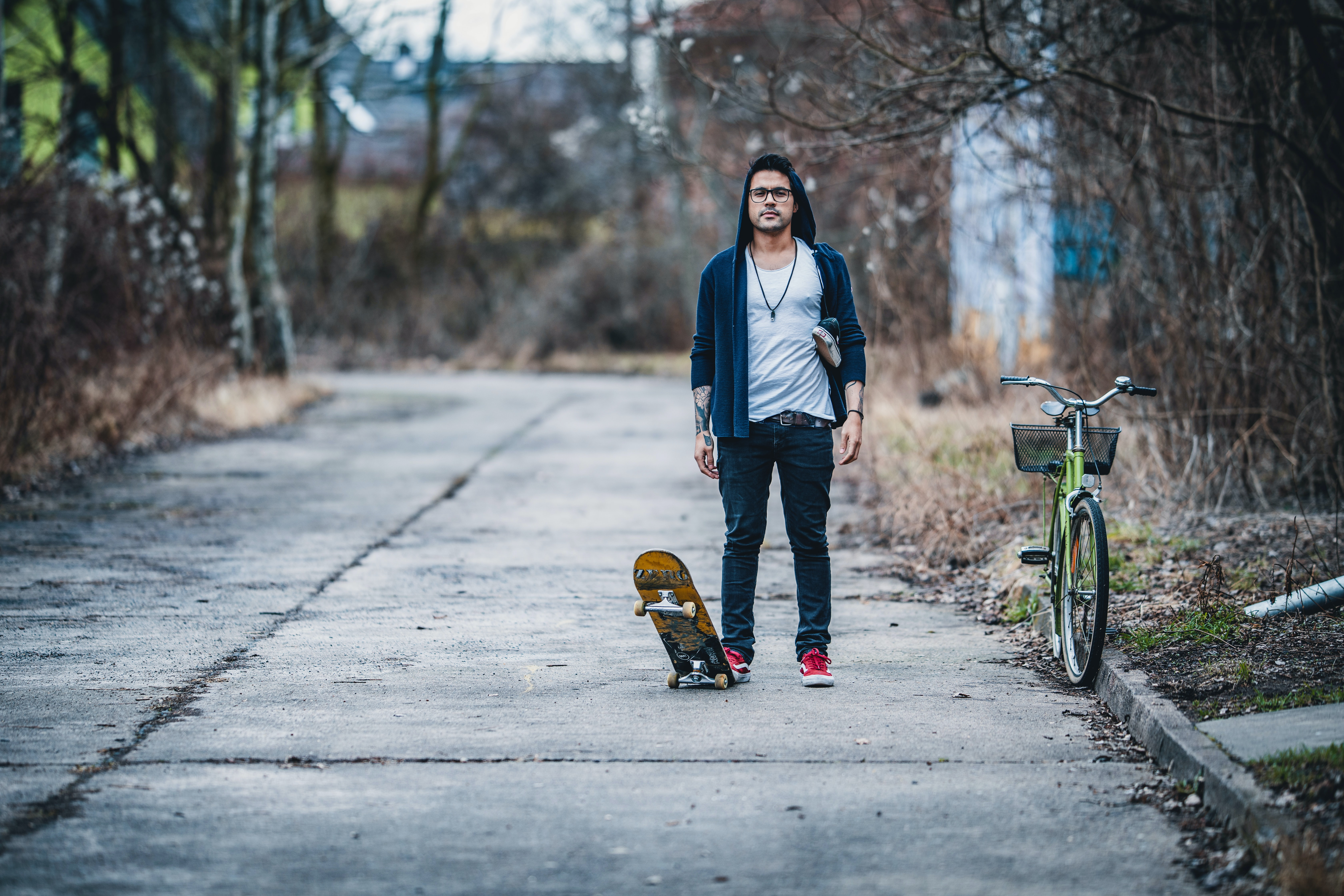 man playing a skateboard beside green city bicycle