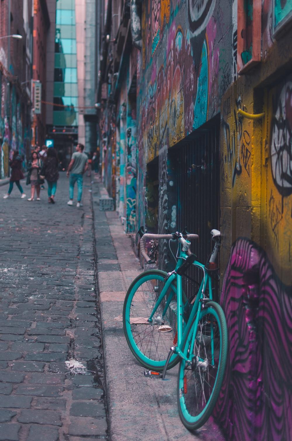 green road bike parked on wall street