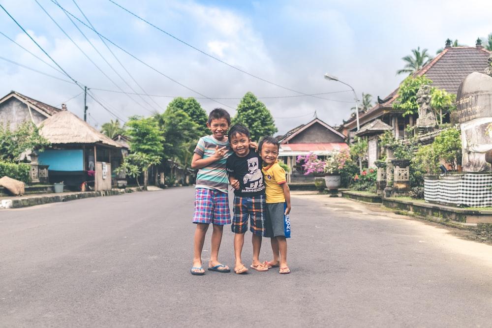 three boy standing on road