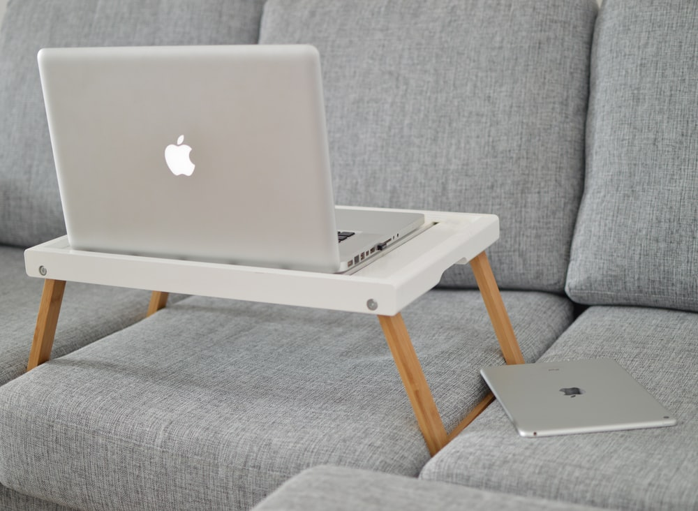 silver MacBook on laptop table on sofa