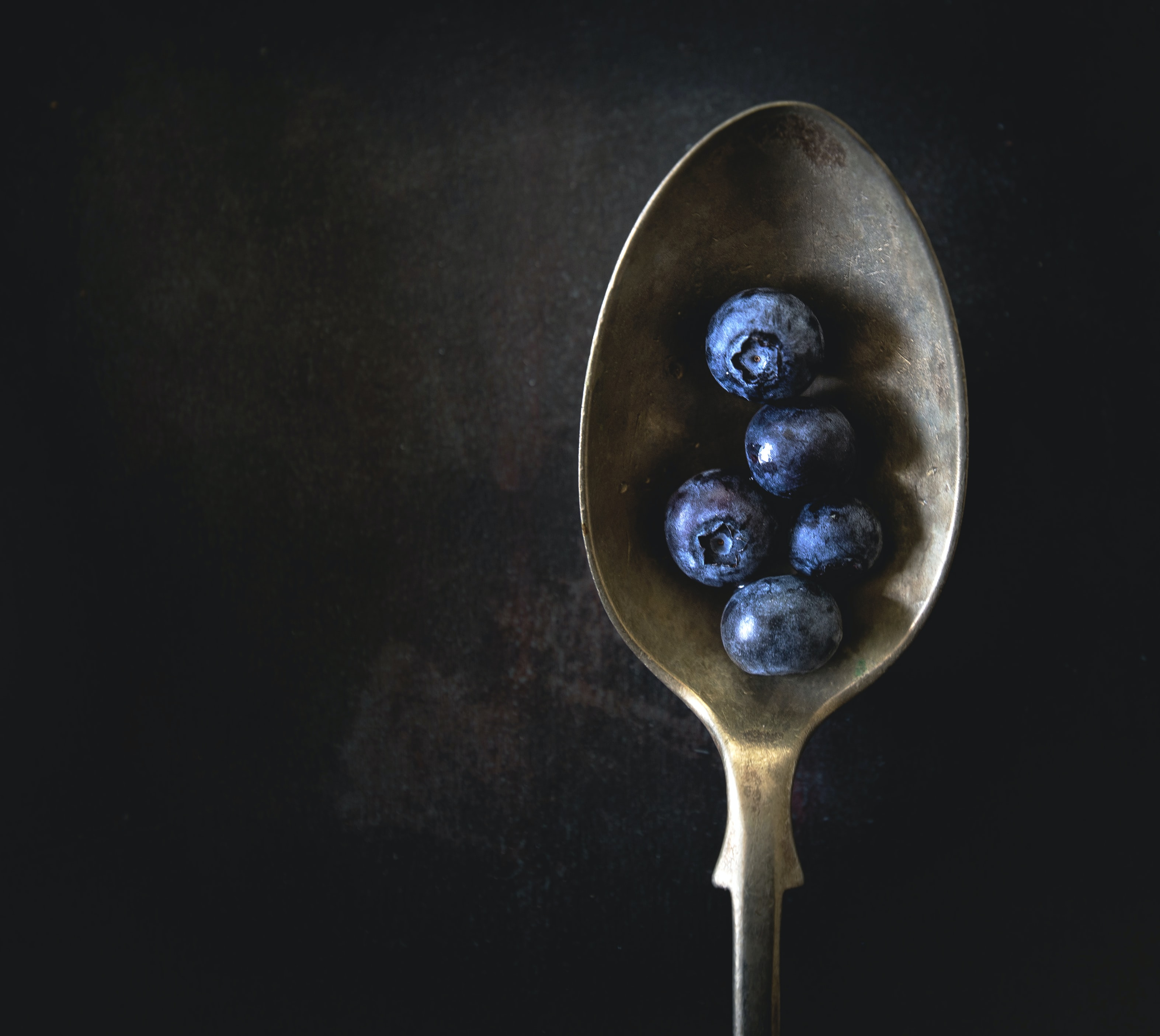 five blueberries on gold spoon