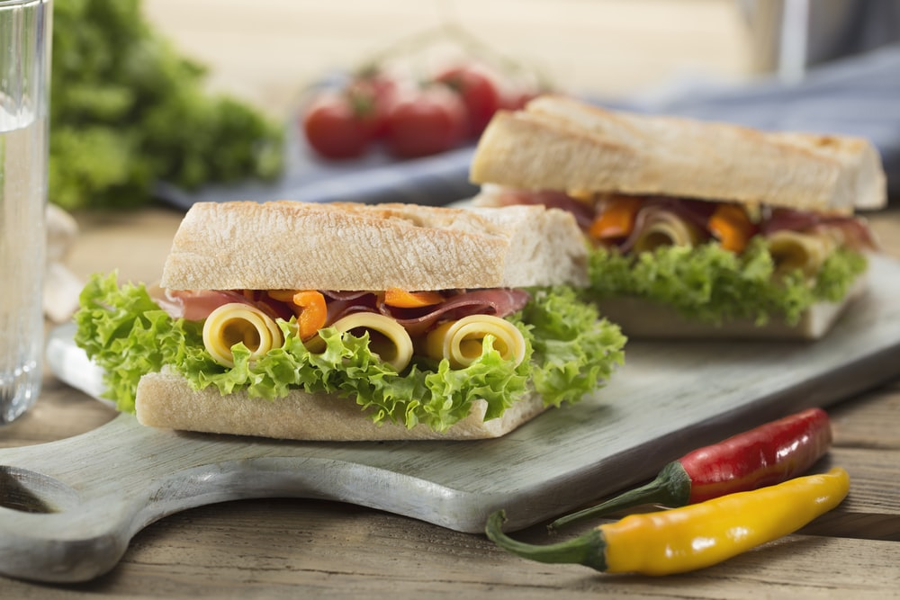 sandwich with lettuce and cheese served on chopping board