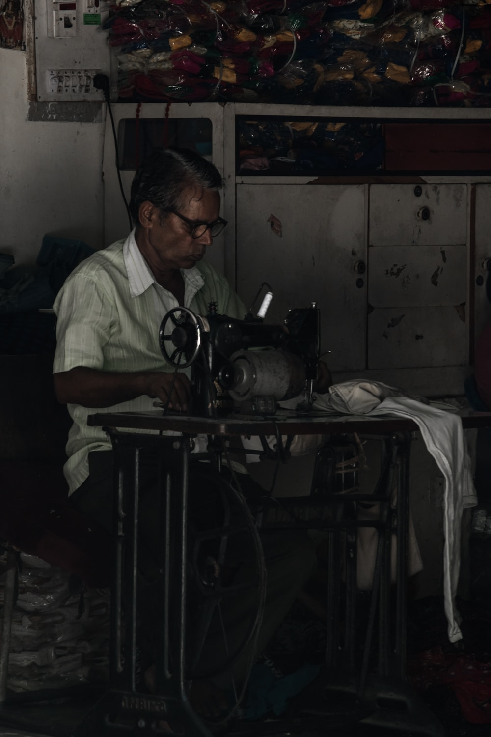 man sitting on chair working on sewing machine