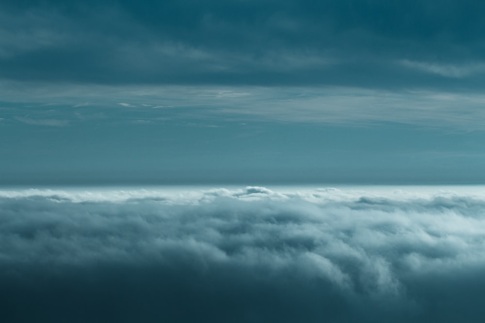 white clouds under teal sky