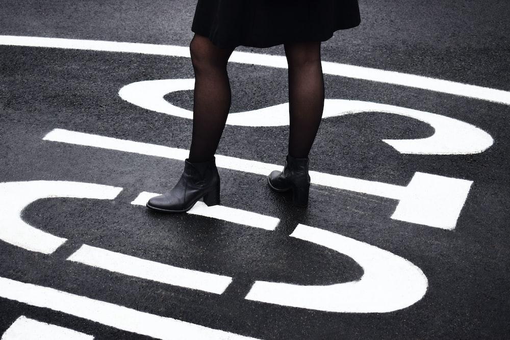 woman standing on black asphalt road