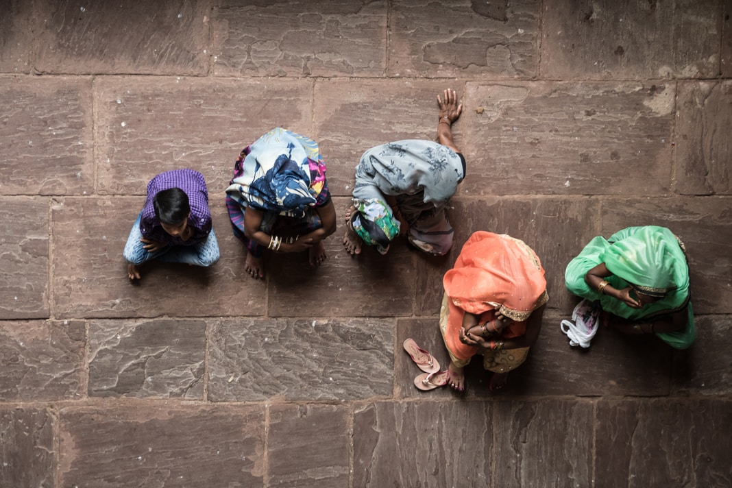 five person sitting on concrete floor