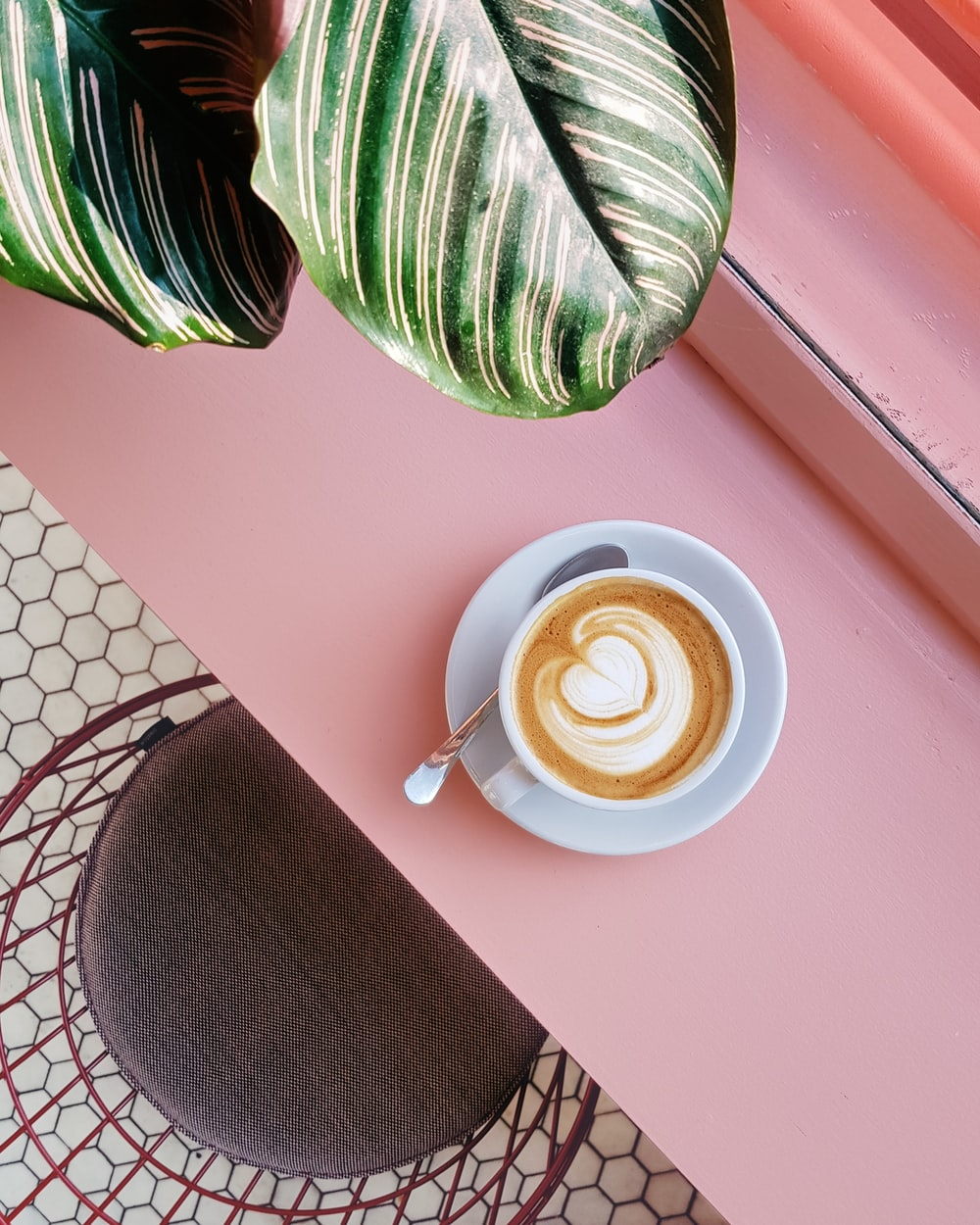 cup of coffee on saucer with teaspoon on pink tabletop