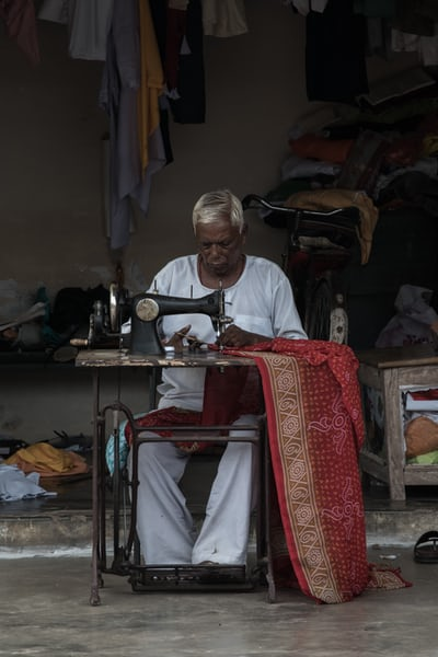 A man sewing garment