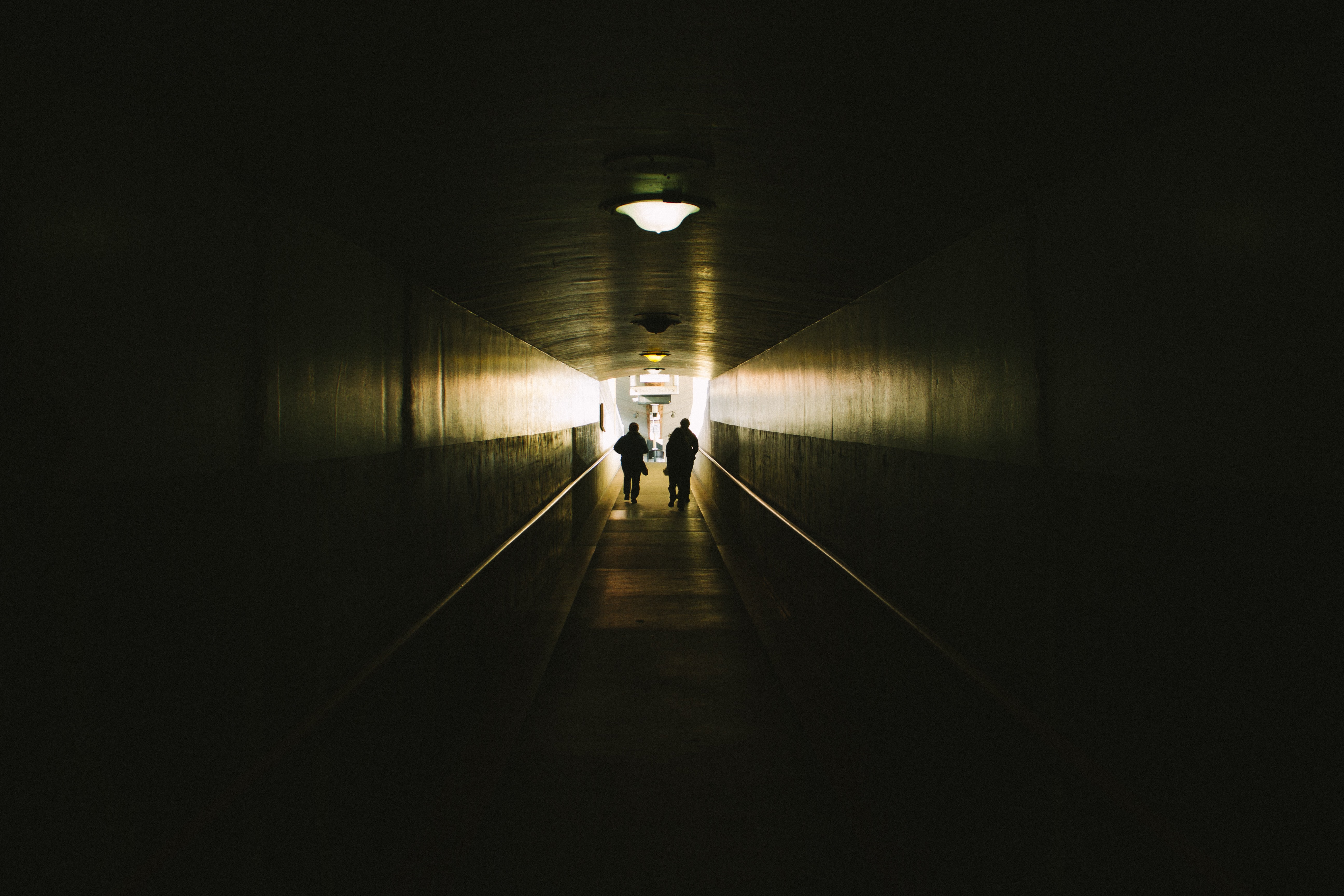 two person walking between concrete walls