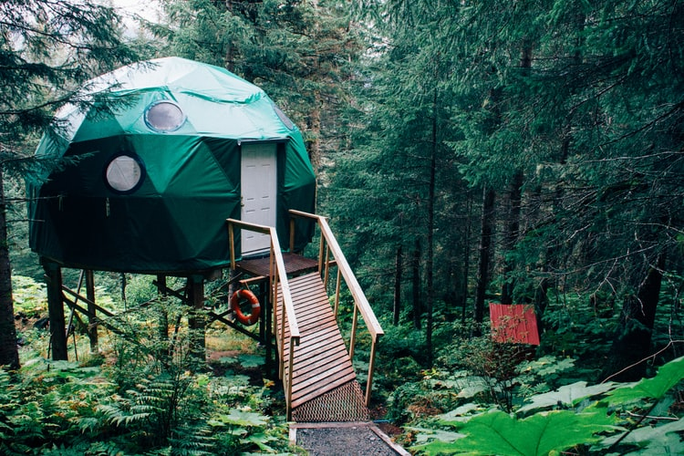 In the woods, there is a geodesic cabin on stilts. It has a ladder leading to the front door and has no windows, covered in some kind of green tarp (but a stretchy one).