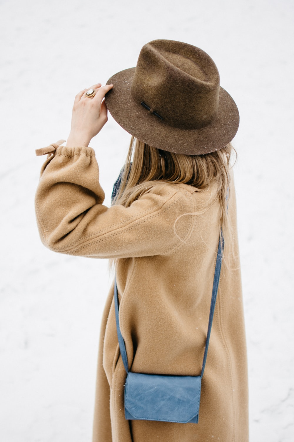 woman holding her hat