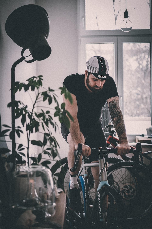man riding on gray rigid bicycle near window