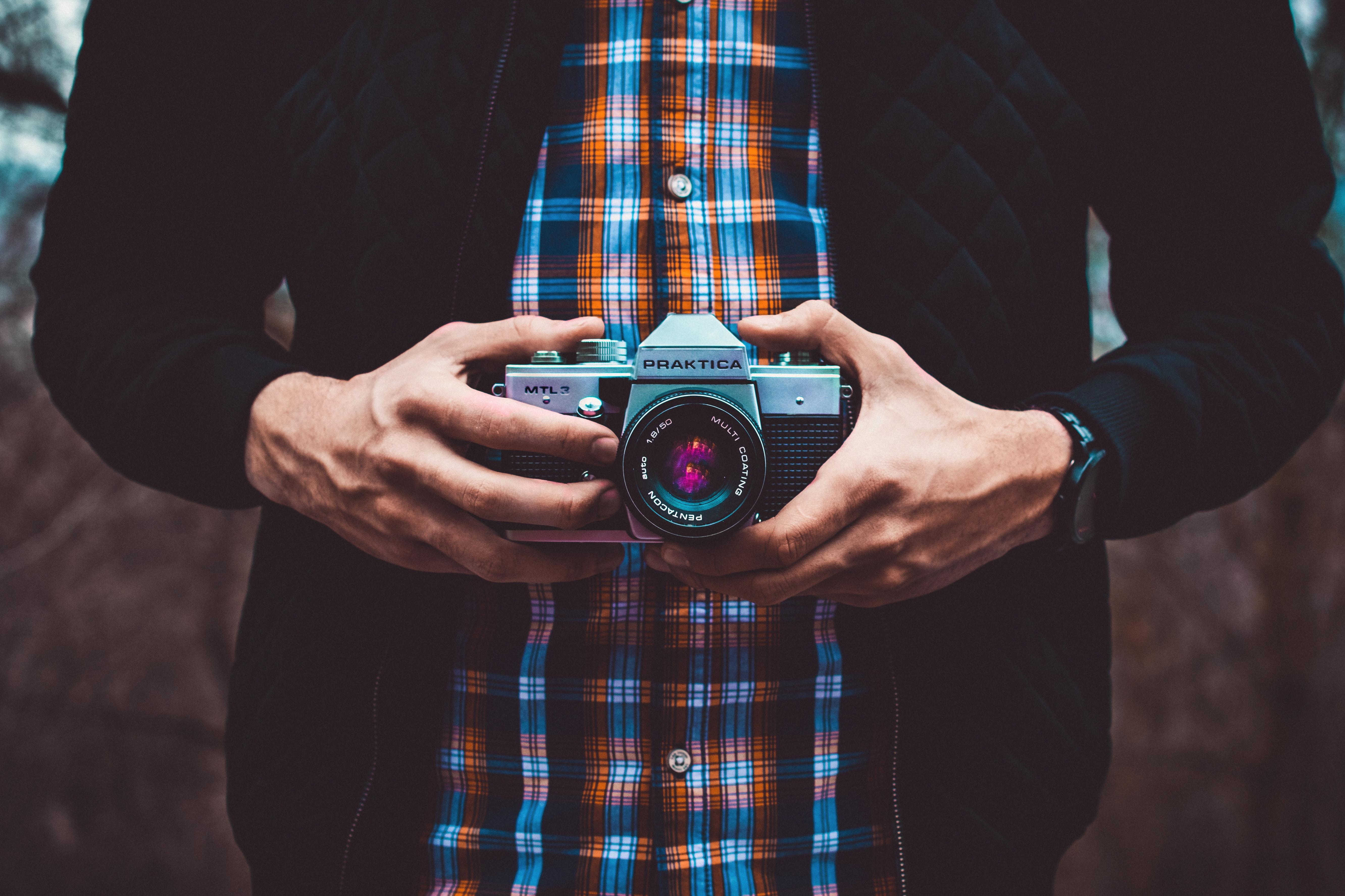 person holding mirrorless camera