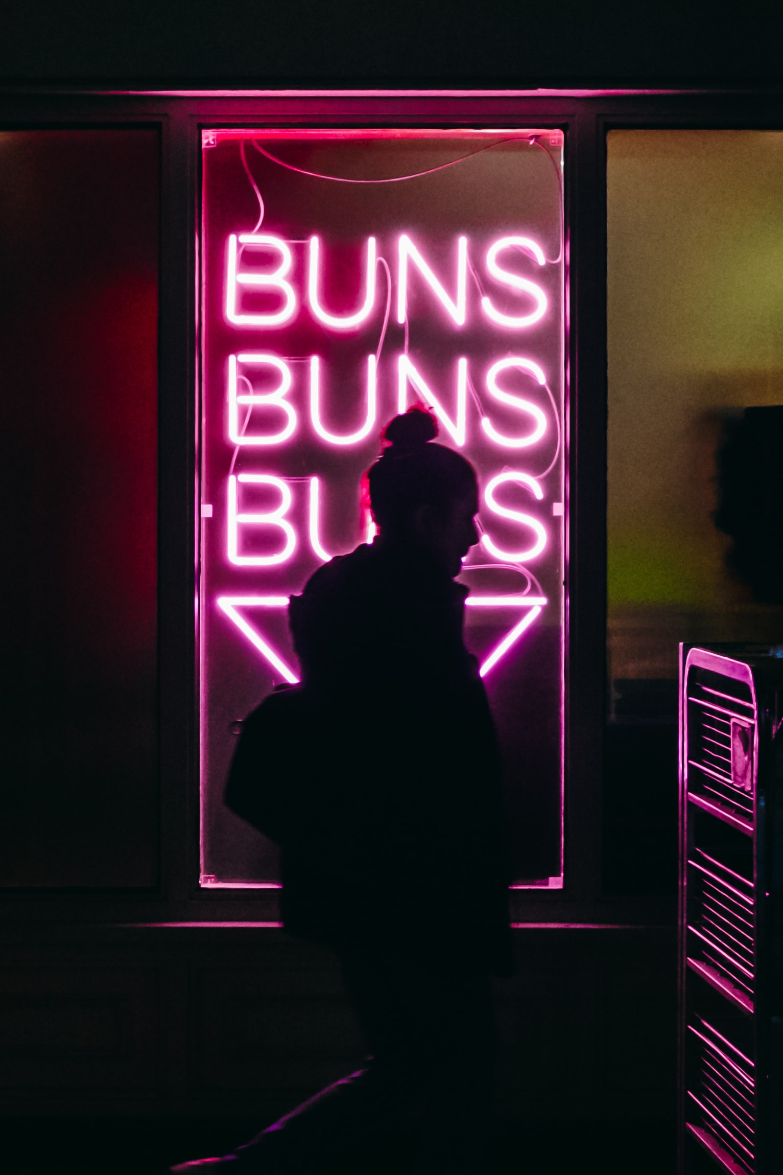 woman standing in front of BUNS LED signage