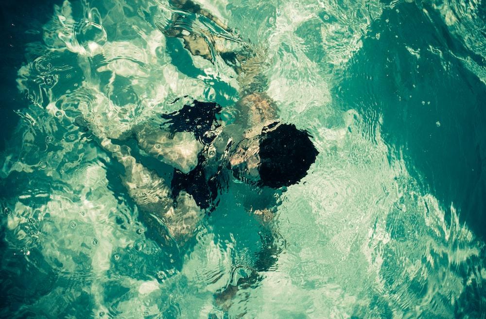 man swimming in green body of water