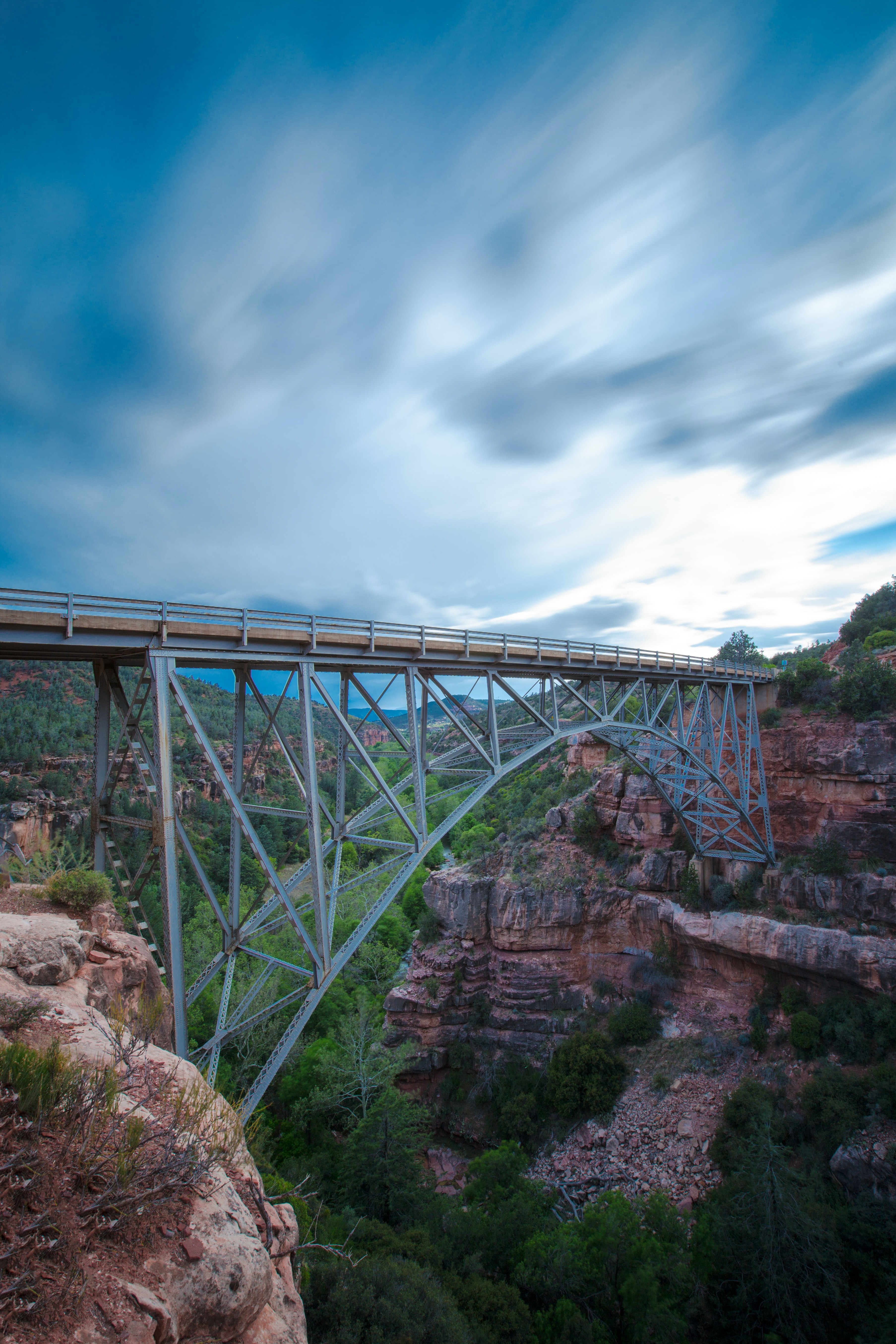 gray bridge between brown rocky mountains under cloudy sky during daytime