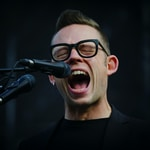 shallow focus photography of man shouting using microphone