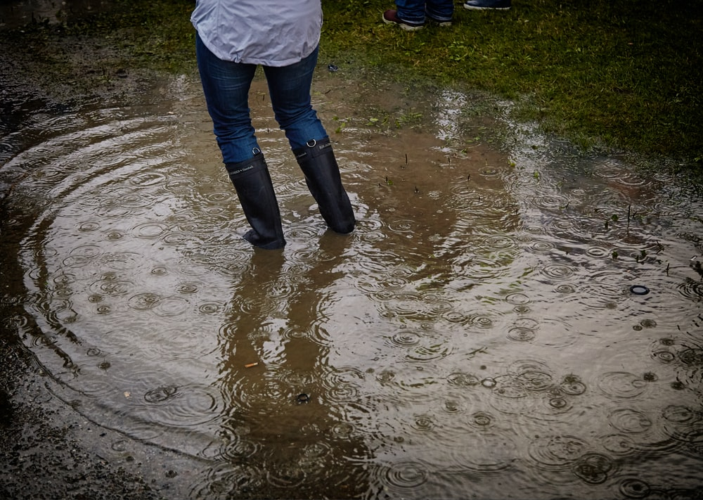 person with rain boots standing on body of water
