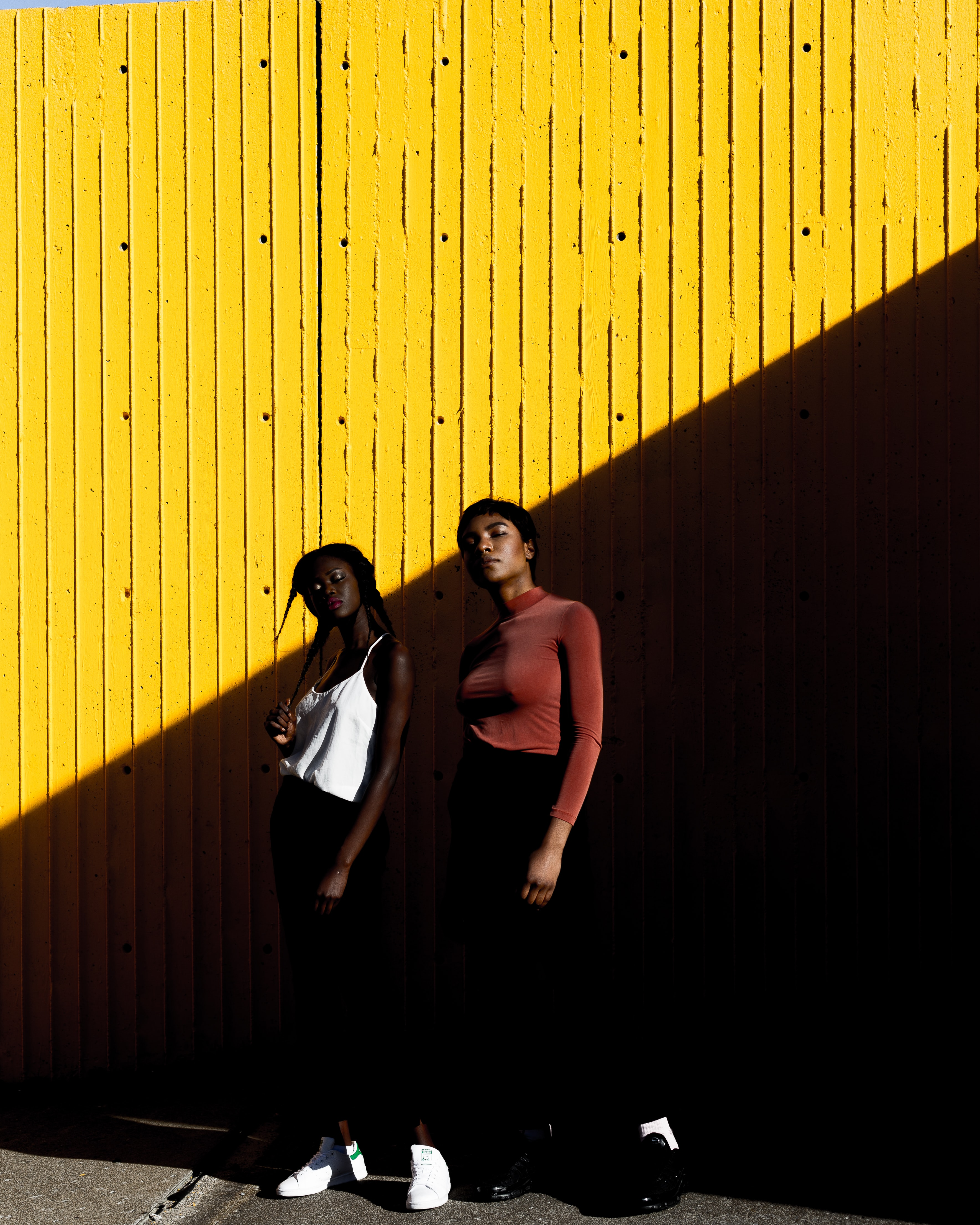 two women standing in front of yellow wall